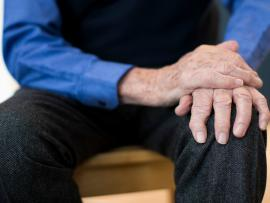 man with esential tremor holding hands on lap