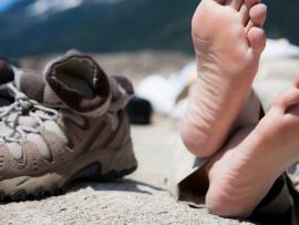 hiker rests in bare feet next to hiking shoes and socks