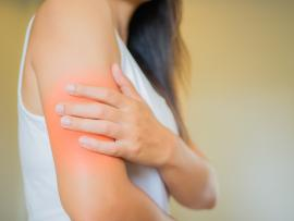side view of woman in white tank top with pain in upper arm