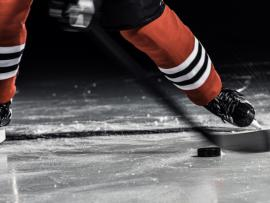 hockey player on the ice about to hit the puck