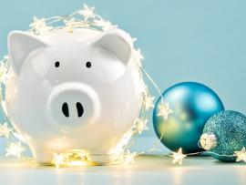 white piggy bank surrounded by holiday decorations on a blue background