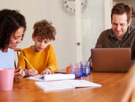 homeschool parents working with child at kitchen table
