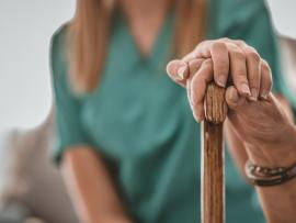 closeup of caregiver's hand holding elderly hand which is holding a cane