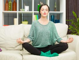 a woman sitting on her couch cross legged and meditating