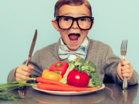 little boy of 50s era clothing is ready to eat his veggies!