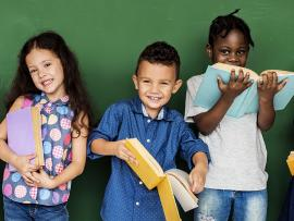 elementary kids in classroom holding books in front of chalkboard