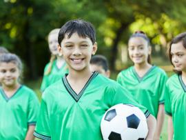 latino tween boy holding a soccer ball with soccer team.