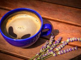 A blue mug of hot homemade latte set on a picnic table with springs of fresh lavender beside it.