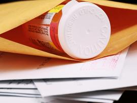 closeup of a prescription bottle in a mail order envelope