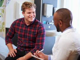 young male patient consulting with doctor in examination room