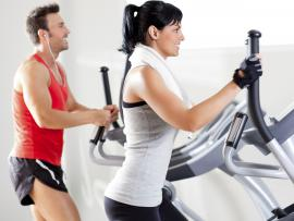 man and woman working out on elliptical machine