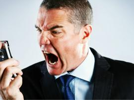 business man yelling at cell phone