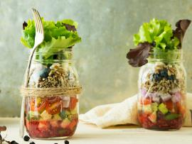 two glass mason jars filled with salad ingredients