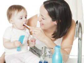 mom brushing baby's teeth with a small toothbrush
