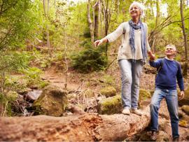 older couple hiking in the woods. man holding woman's hand as she crosses over a log.