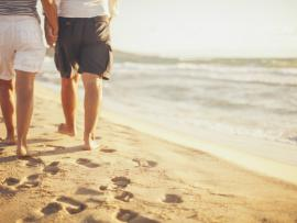 older couple walking barefoot on beach in shorts.