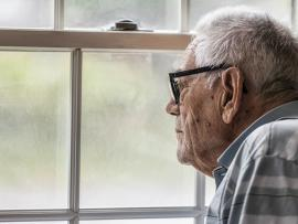 older man with dementia looking out window of home