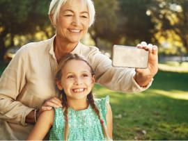 grandmother taking a picture with granddaughter in the park