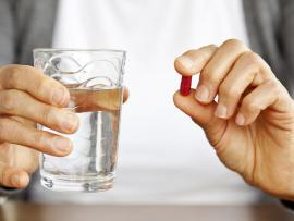 person holding pill with glass of water