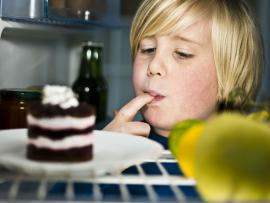 overwight child sneaking dessert in refrigerator