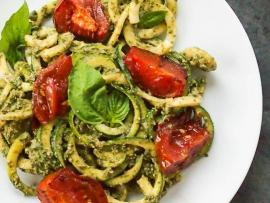 plate of fresh zucchini zoodles with a pesto sauce topped with roasted tomatoes