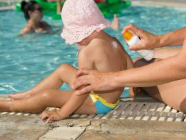 woman putting sunscreen on child by the pool