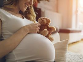 pregnant woman smiling and holding a teddy bear to tummy
