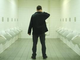 man standing in public bathroom with urinals on each side