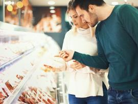 man and woman choosing packaged meat in the grocery store
