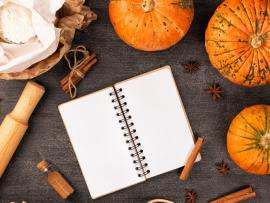 tabletop with small pumpkins scattered and a rolling pin and recipe book