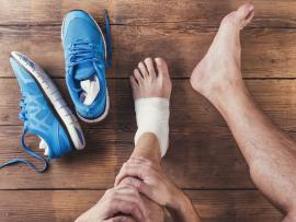 man with bandaged left foot sits on hardwood floor next to his running shoes