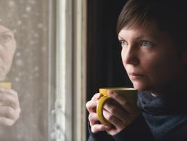 sad woman looking out window holding a cup of tea