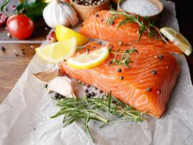 Closeup view of a salmon filet on top of parchment paper on a wooden table, with rosemary sprigs and lemon wedges on top and several heads of fresh garlic behind it.