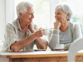 happy senior couple enjoying a cup of coffee in the comfort of their own home