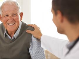 senior man at health examp speaking with doctor