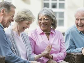 seniors laughing and engaging in a happy conversation