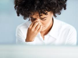 woman with curly hair facing forward with a hand on her face indicating sinusitis