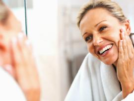pretty middle aged woman checking out her great skin in the mirror