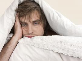 very tired looking man in bed under the covers