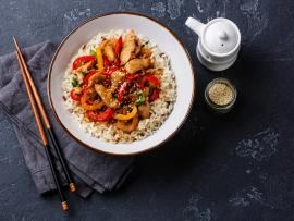 Chopsticks and a plate of stir-fry chicken, colorful peppers and rice arranged on a slate gray table.