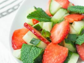 Close up of fresh stawberries, cucumbers and herbs in a white ceramic bowl on a wooden plank table.