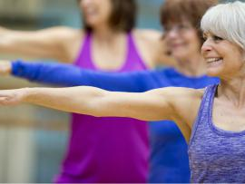older woman working out her arms in a fitness class