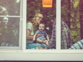 young family looking outside window indicating covid-19 social distancing