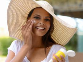 woman wearing a wide brimmed hat in the sun and putting on sun screen
