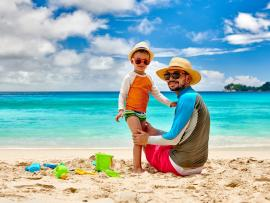 dad and toddler at beach wearing sunshirts hats and sunglasses