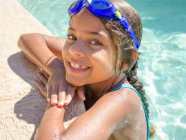 tween latino girl with goggles hanging on the edige of the pool smiling