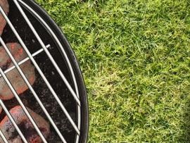 hot grill next to football with grass in background indicating tailgate party