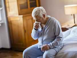 senior man sitting on bed blowing his nose