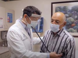 Carilion Clinic Structural Heart specialist surgeon wearing PPE examines patient
