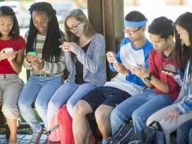 diverse group of teens looking at social media on their phones